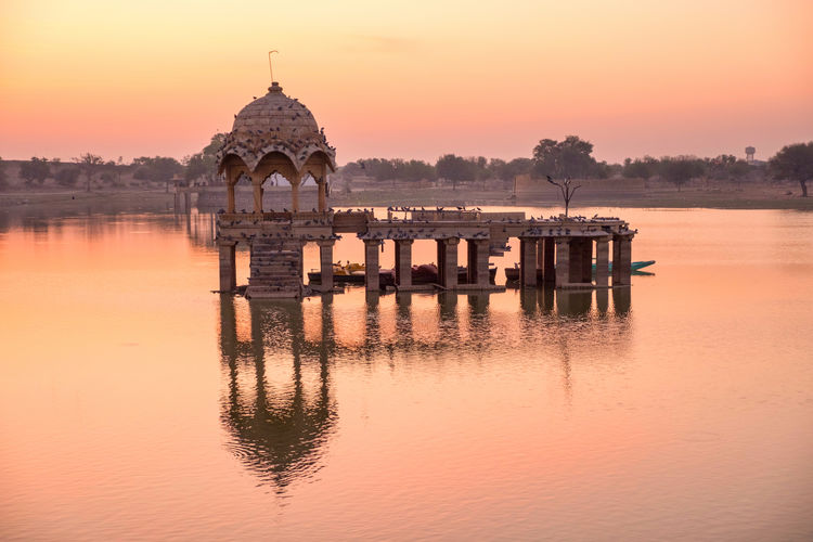 Sunrise over stone tower in Gadi Sagar lake, Jaisalmer, India. Architecture Beauty In Nature Building Building Exterior Built Structure Gadisagar Temple Gadisarlake Historical Jaisalmer Lake Nature No People Orange Color Outdoors Reflection Religion Scenics - Nature Sky Sunrise Sunset Tourism Travel Destinations Water Waterfront