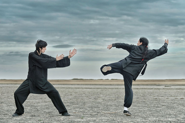 People practicing martial arts on land against cloudy sky