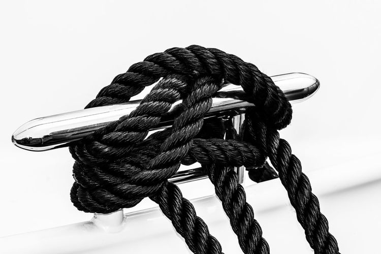 Close-up of rope tied metal bollard