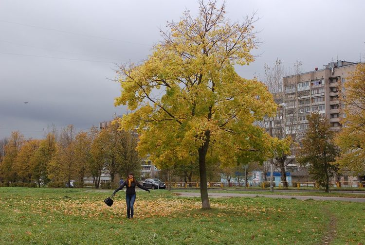 Woman walking in park on overcast autumn day