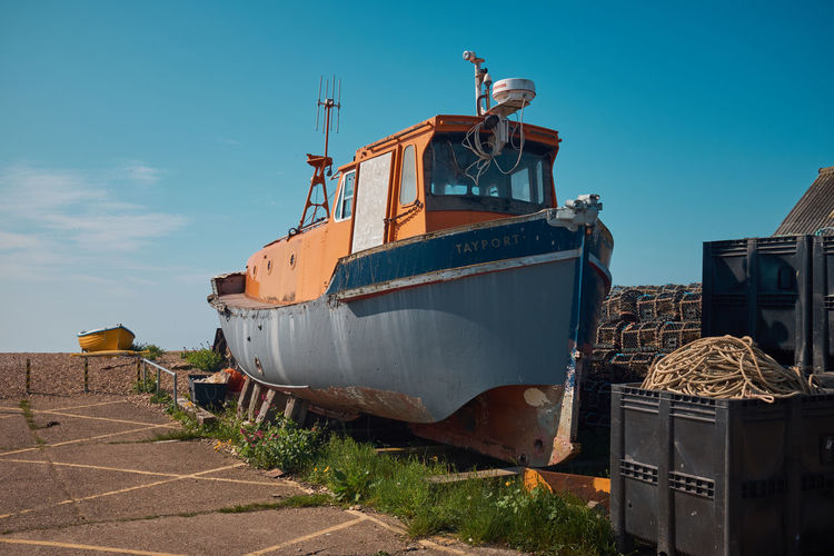 Rusty ship moored at shore against blue sky