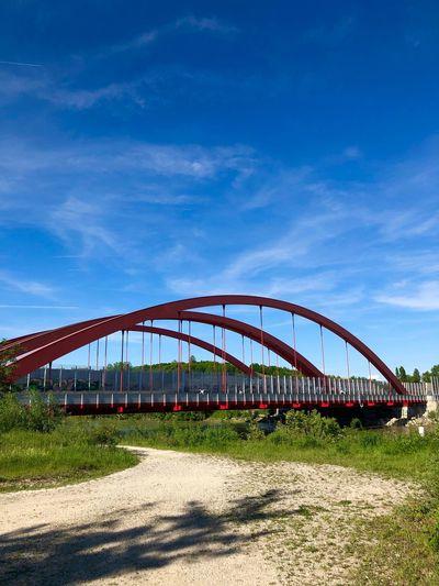 View of bridge on field against blue sky