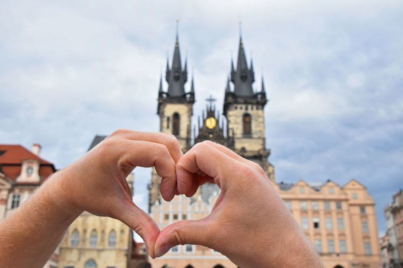 Cropped image of person making heart shape with hands against building in city