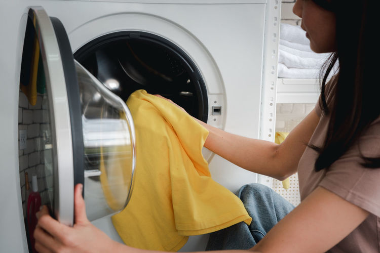 Midsection of woman washing clothes in machine at home