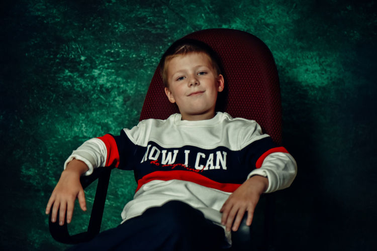 Portrait of smiling boy sitting on chair