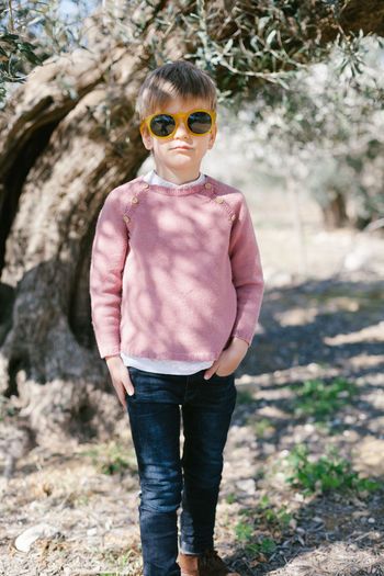 portrait of boy wearing sunglasses standing outdoors Kids Pink Wood Boy Casual Clothing Day Fashion Front View Leisure Activity Lifestyles Looking At Camera Nature One Person Outdoors Portrait Real People Standing Sunglasses Tree Young Adult Young Women Be. Ready.
