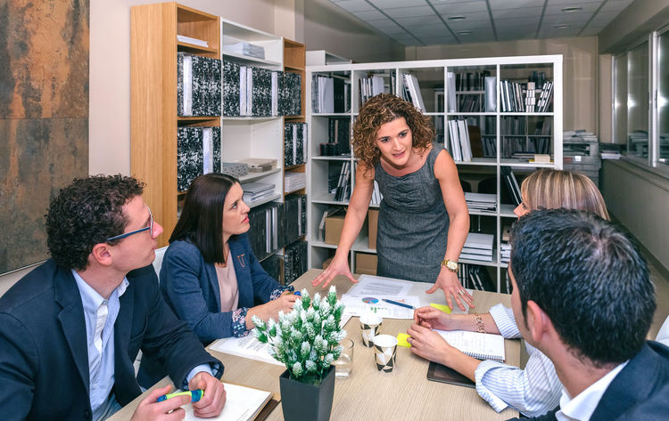 Businesswoman talking in a business meeting to teamwork sitting at table in company headquarters Business Company Horizontal Innovation Man Meeting Office Teamwork Woman Working Workplace Business Finance And Industry Businessman Businesspeople Businesswoman Colleague Connection Group Headquarters Leadership Networking People Sharing  Success Team