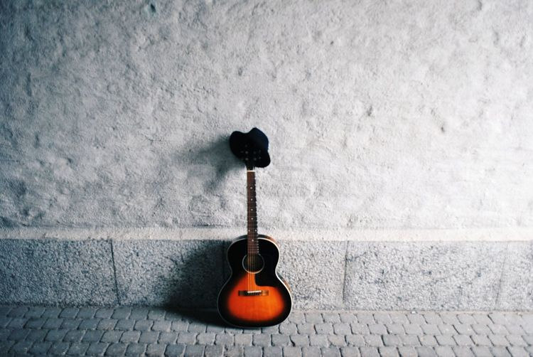 Guitar standing against a wall