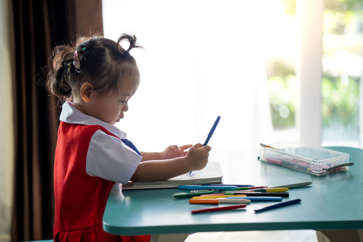 Side view of girl drawing in book at table