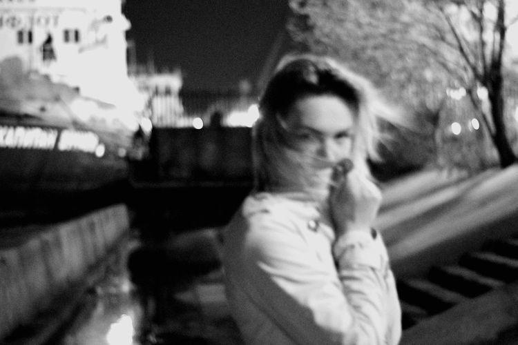 Reflection of man smoking cigarette on city street at night