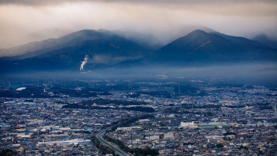 Dramatic and dark process cityscape in a strom and smog layer mountain background in japan