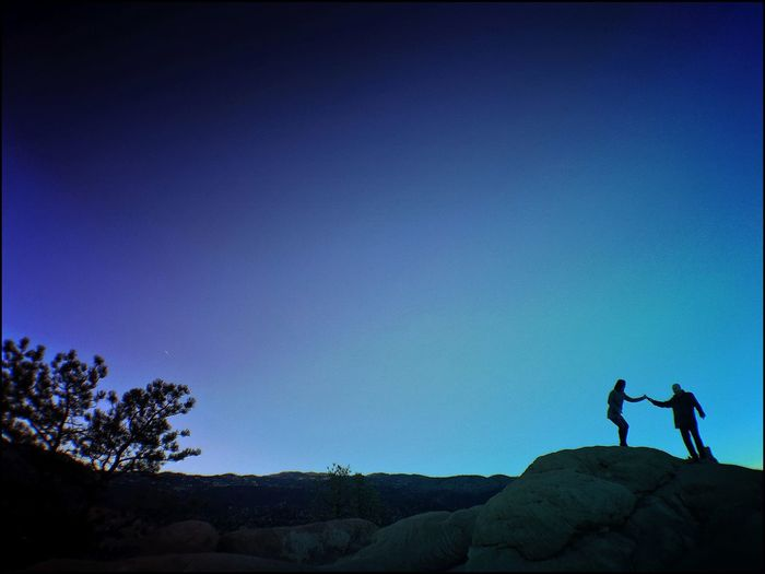 Silhouette of people standing on mountain against clear sky