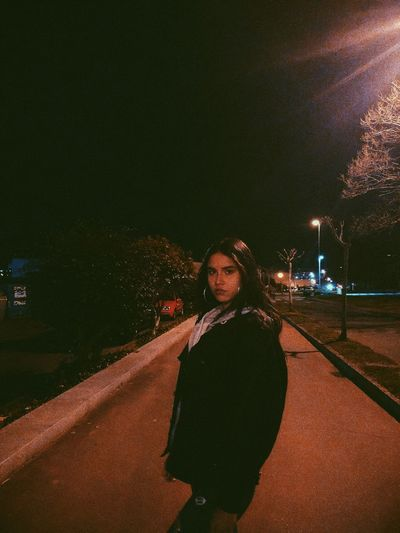 Portrait of woman standing on road at night