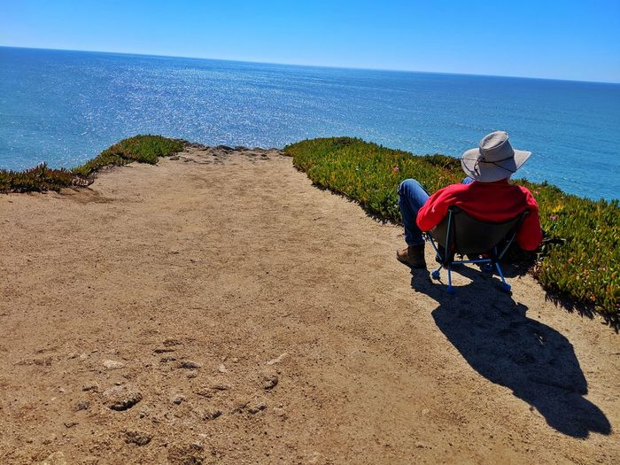 Contemplating the vastness of nature. The ocean. Man in chair relaxing into Nirvana. Man Single Solitude Sandstone Cowboy Hat Hat Red Jeans Boots Stretched Lounging Alone View Blue End Path Overlook Background Zen Therapeutic Peaceful Soil Dirt Clear Sky Sky Hiker Horizon Over Water Ocean Calm Sea Seascape