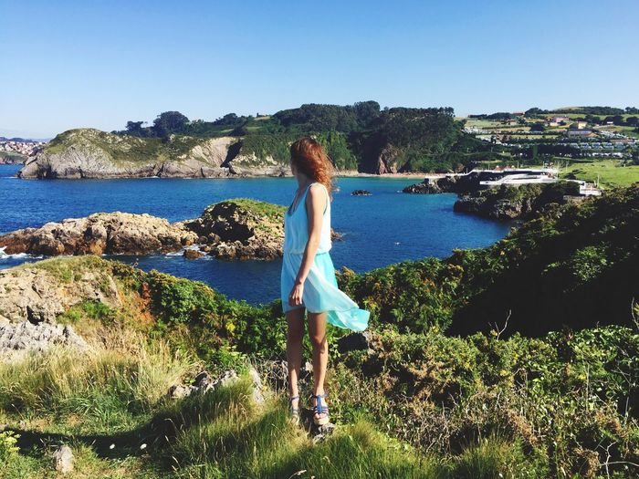 Real People One Person Water Clear Sky Leisure Activity Rear View Nature Standing Lifestyles Sea Day Casual Clothing Outdoors Full Length Rock - Object Beauty In Nature Plant Blue Scenics Women One Person Only Landscape Fashion Location