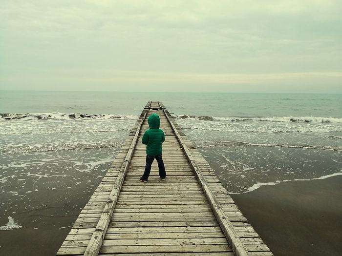 Rear view of boy standing on pier over sea