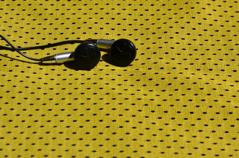 High angle view of earphones on yellow fabric