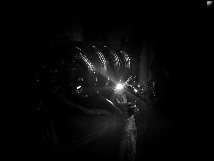 Man holding illuminated fire in dark room