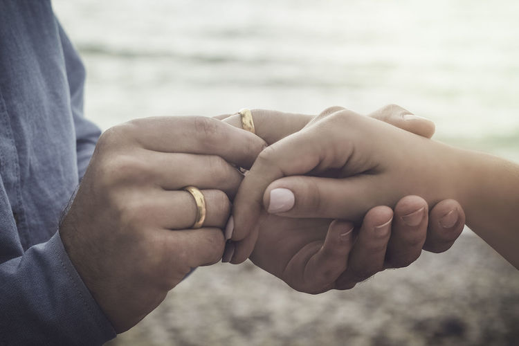 Midsection of man putting engagement ring on woman finger at beach