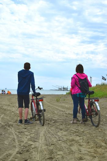 Rear view of friends with bicycle standing at beach against sky