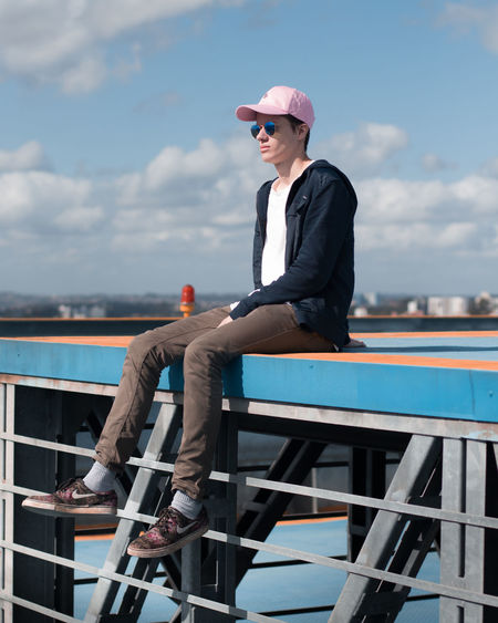 Cap Cloud - Sky Day Full Length Leisure Activity Lifestyles Nautical Vessel One Person Outdoors Portrait Railing Real People Sea Sitting Sky Water Young Adult Young Men