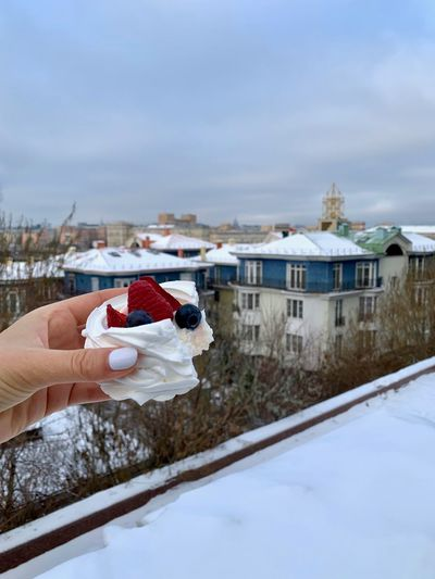 Dessert pavlova in a hand with moscow view