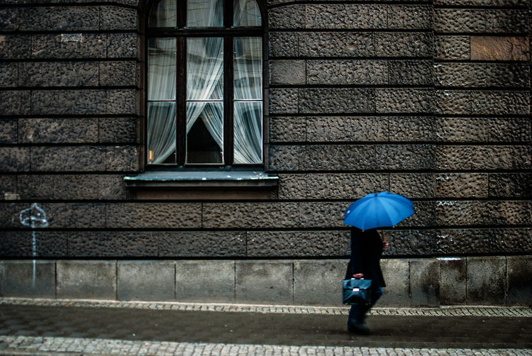 Person with umbrella walking on sidewalk against building