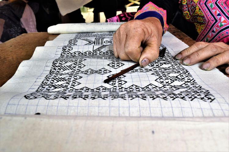 Cropped image of woman making artwork on fabric