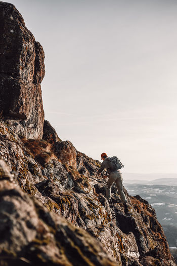 Man rock on mountain against sky