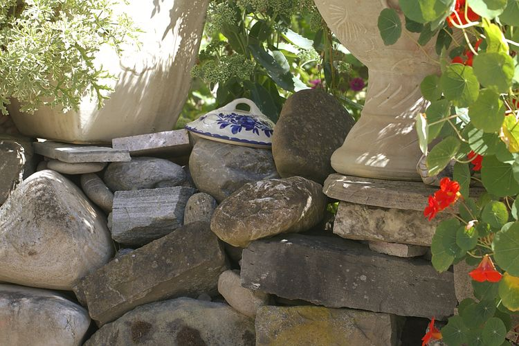 Stone wall by rocks and trees