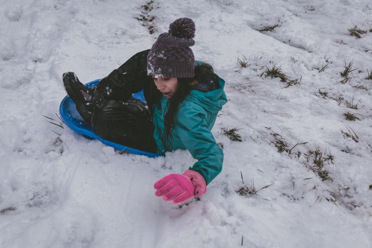 Full length of girl sitting on bobsled in snow