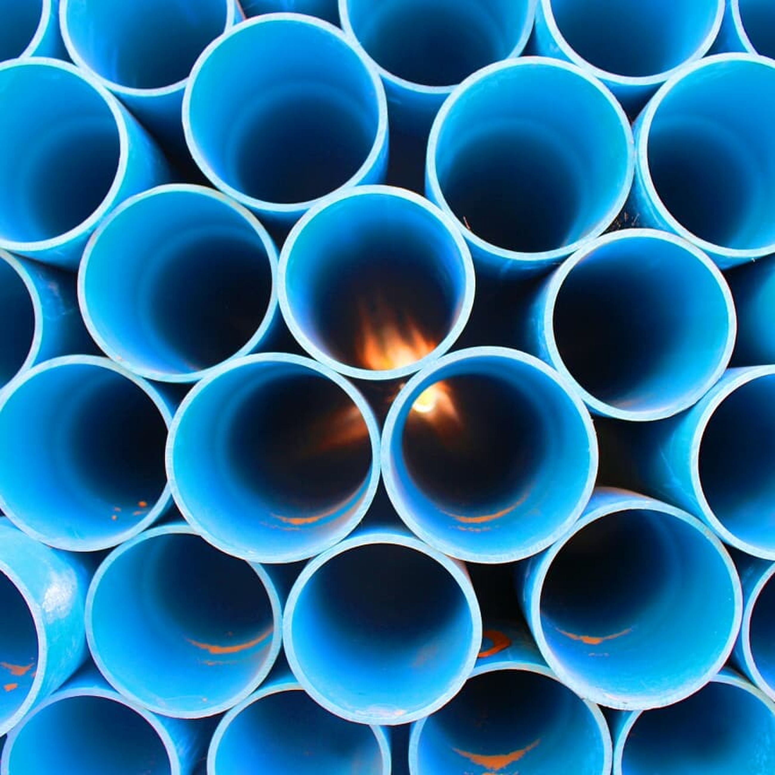 large group of objects, blue, full frame, stack, repetition, backgrounds, shape, geometric shape, circle, no people, in a row, abundance, pipe - tube, pattern, industry, order, tube, cylinder, indoors, blue background