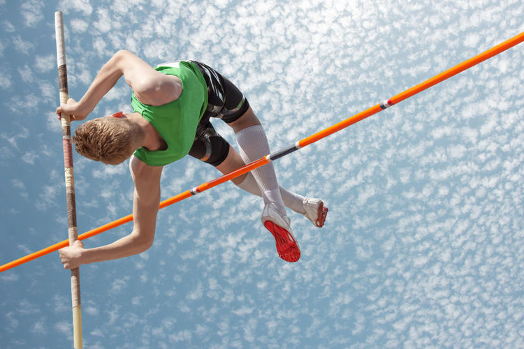 Pole vaulter over the bar High Jump Pole Vaulter Pole Vaulting Day Jumping Leisure Activity Nature One Person Outdoors People Real People Sport Water