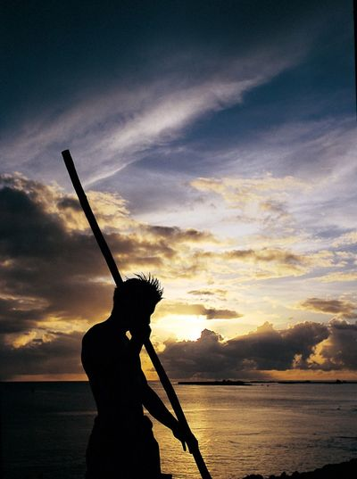 Silhouette Man With Bamboo At Sea Shore Against Sky During Sunset