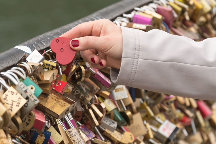 Close-Up Of Love Locks Hanging On Chainlink Fence