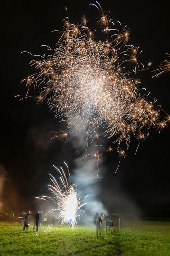 Firework display on field at night