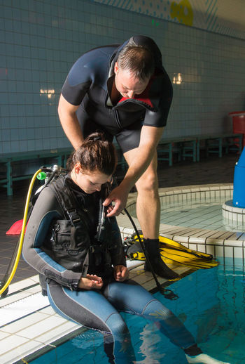 Instructor adjusting woman diving suit at swimming pool