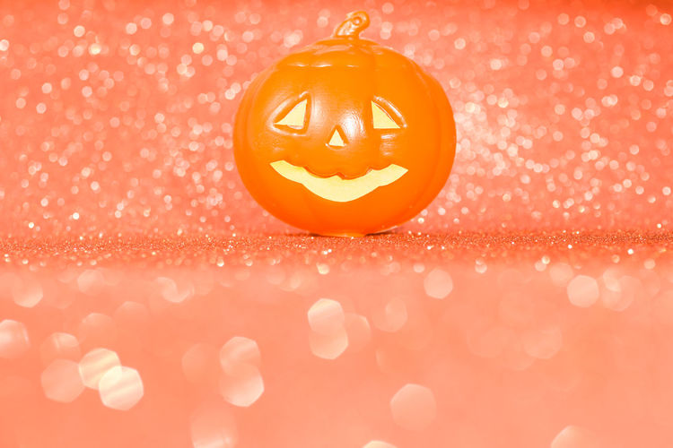 Close-up of pumpkin face against orange background