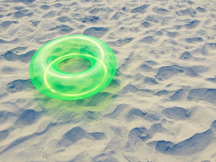 High angle view of green lifeguard ring on sand at beach