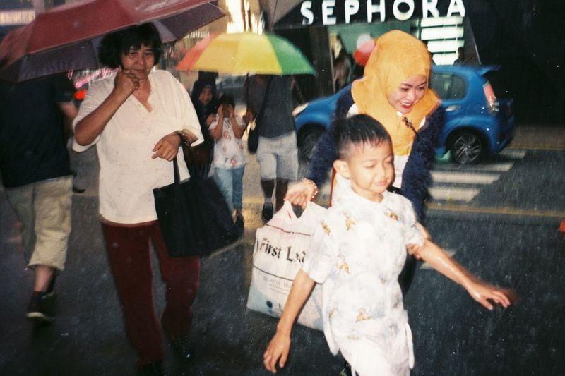 Group of people walking in rain
