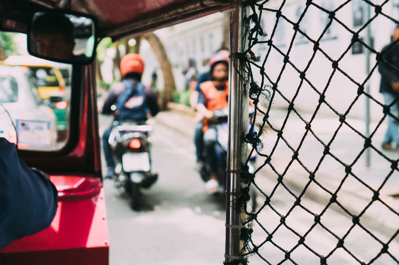 People on street seen through chainlink fence