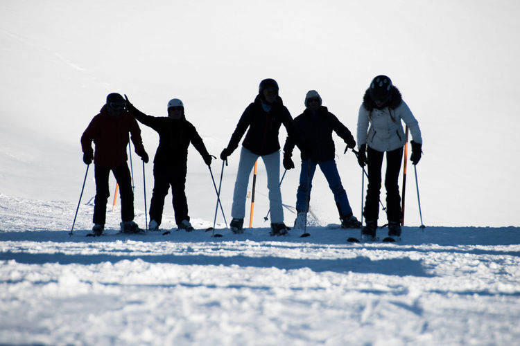 Rear view of friends skiing on snow covered landscape during winter