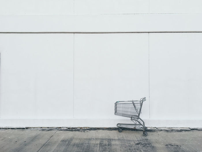 Close-up of shopping cart against white wall