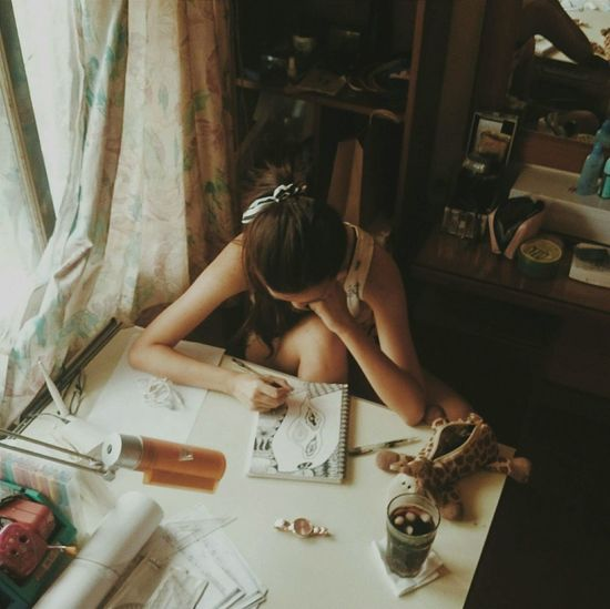 High angle view of young woman drawing on book at table by window in home