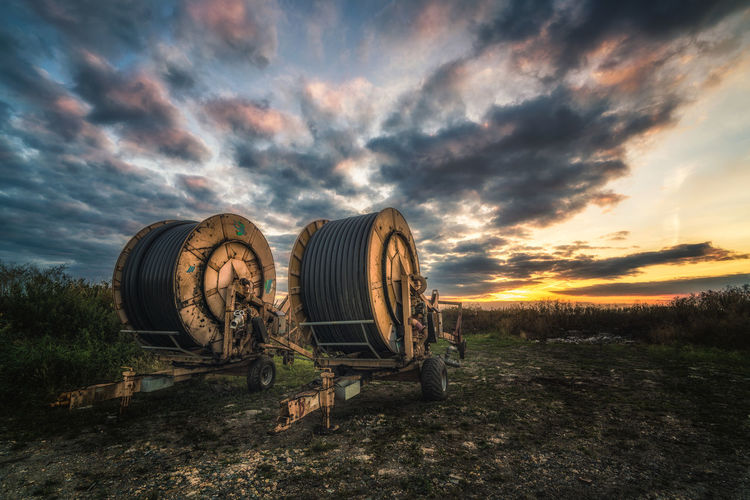 Pipe spools on field against sky during sunset