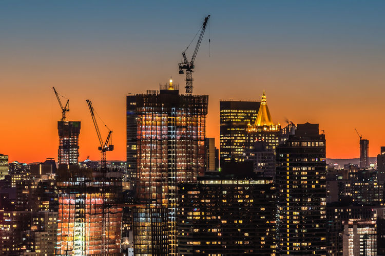 Cranes On Illuminated Modern Buildings Against Clear Sky During Sunset