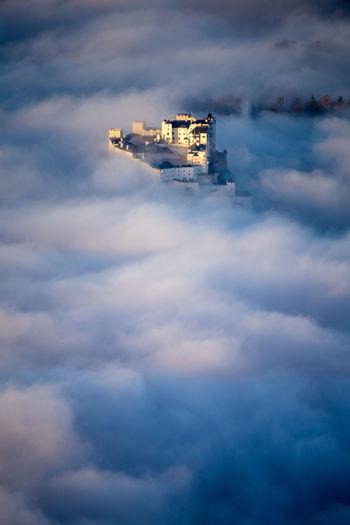 Fortress hohensalzburg rising above a sea of clouds, salzburg, austria