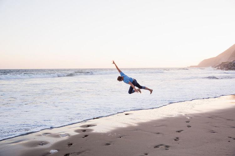Man jumping on beach against clear sky