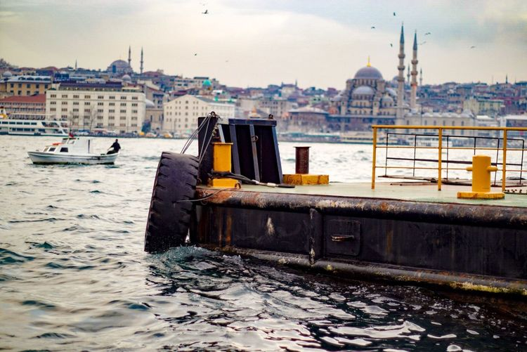Tire at harbor by sea against blue mosque