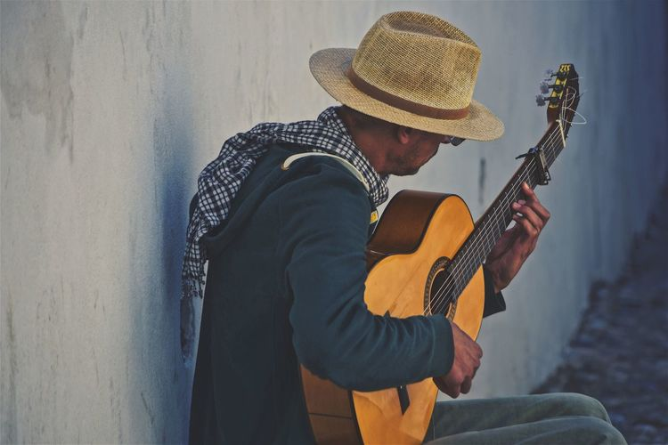 Man playing guitar by wall